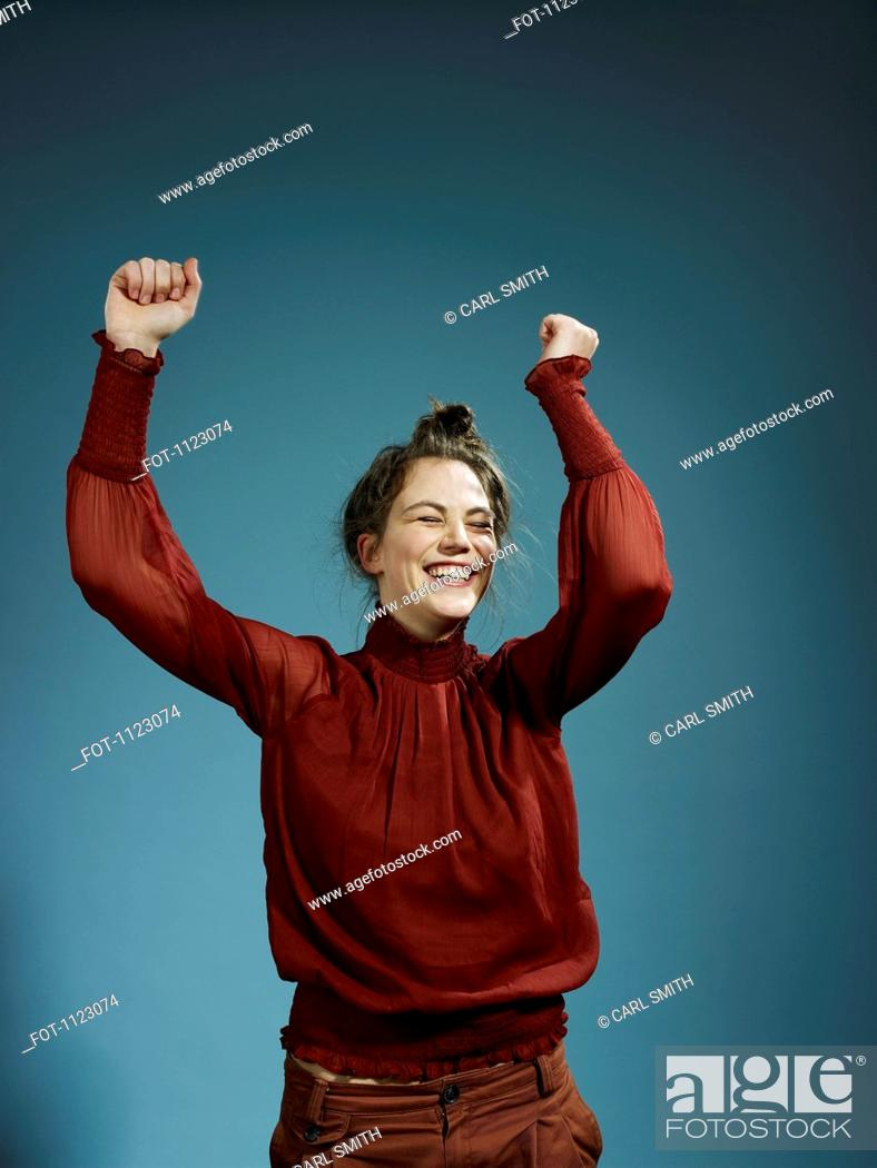 Stock Photo: A young hip woman with her arms raised in celebration.