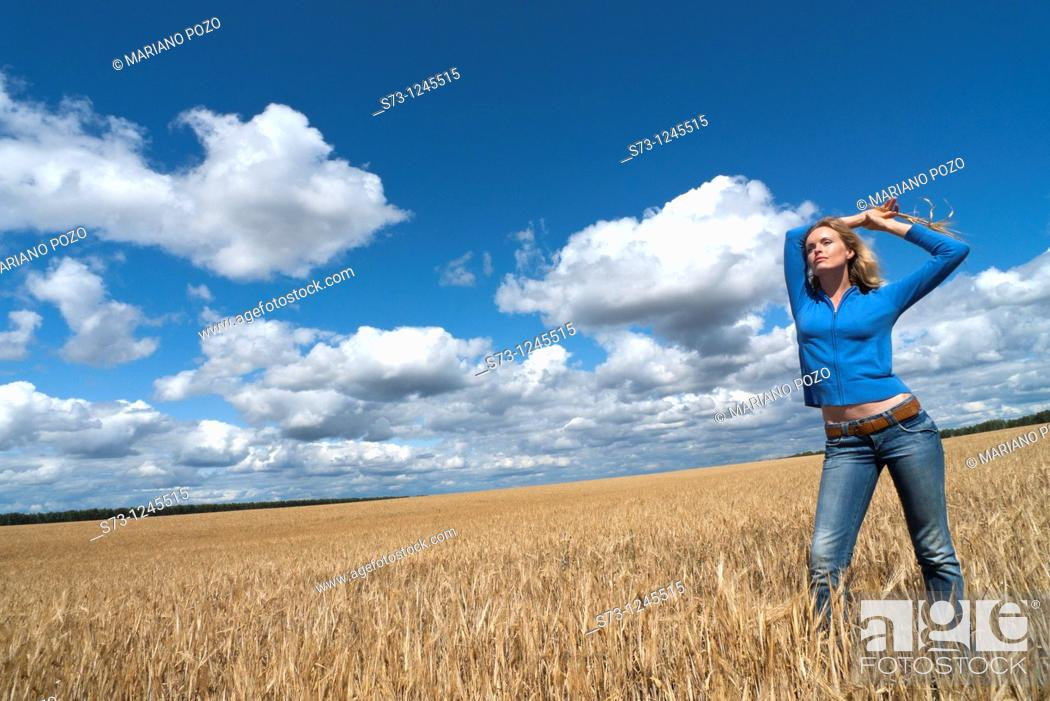 Stock Photo: Young woman in a wheat field in a russian village, Kirillovka, Russian Federation.