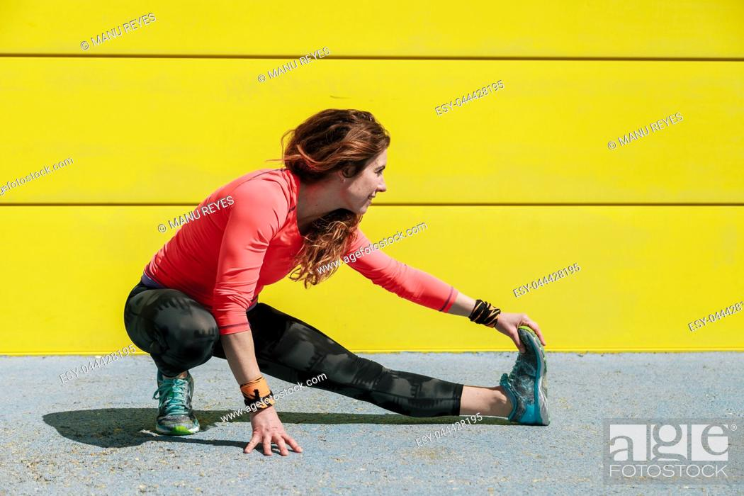Stock Photo: young woman stretching on the floor in front of a yellow wall before running.