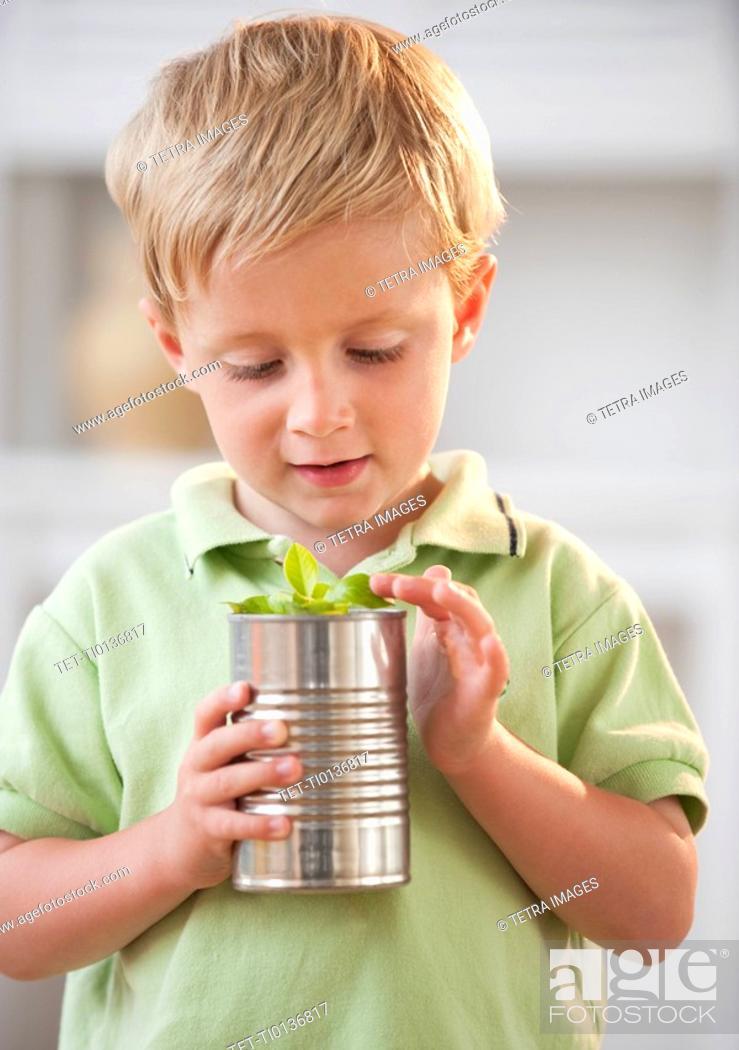 Stock Photo: Child examining plant.