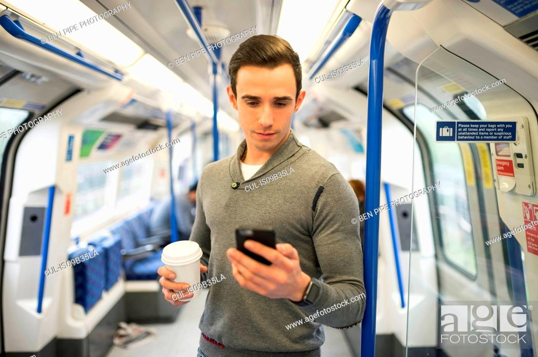 Stock Photo: Man on train looking at smartphone.