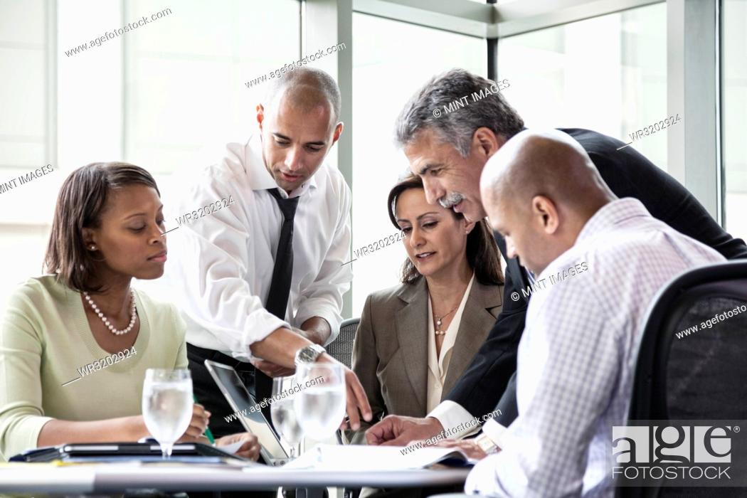 Stock Photo: A mixed race group of male and female business people in a meeting at a conference table next to a large window in a convention centre.