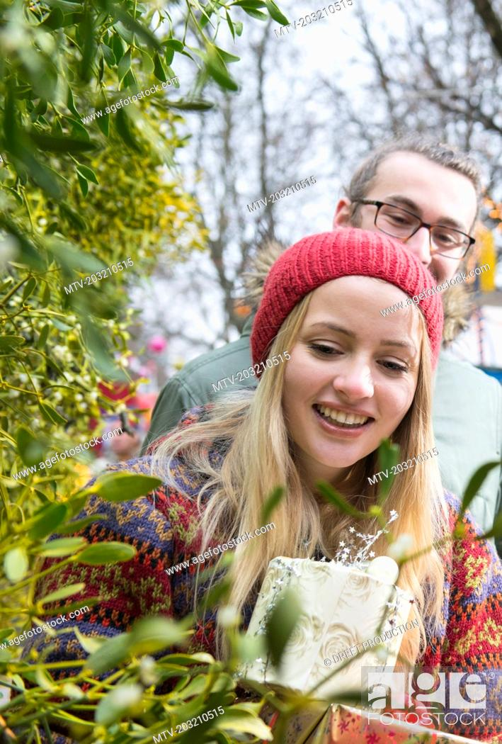 Stock Photo: Young couple with gifts and mistletoe twigs.