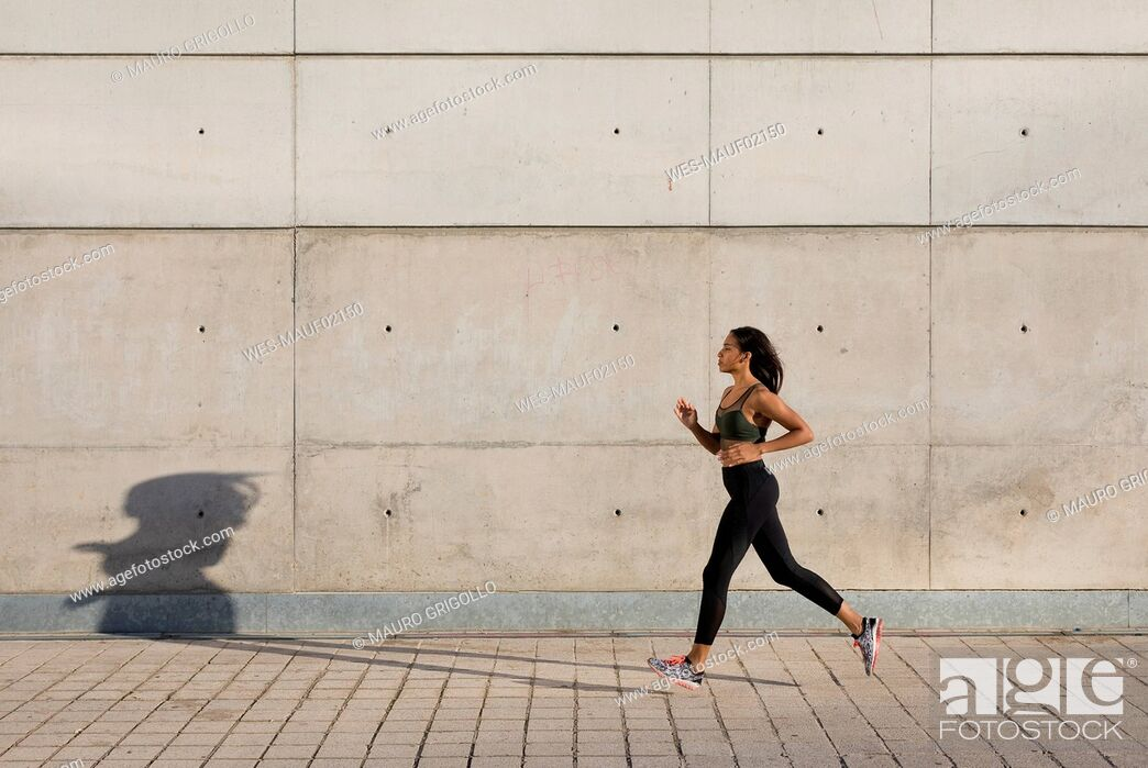 Stock Photo: Young woman running along concrete wall in the city.