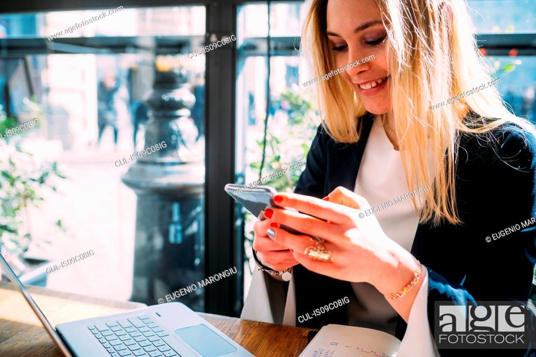 Stock Photo: Young woman at sidewalk cafe table looking at smartphone.