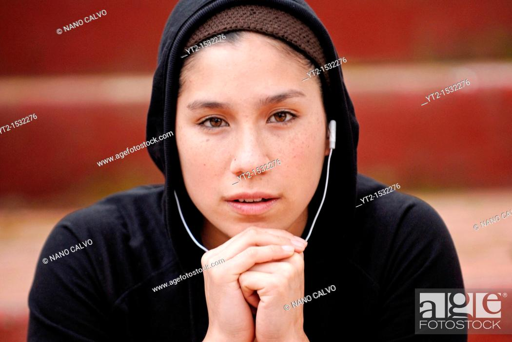 Stock Photo: Young mixed girl, half chinese, half spanish, dressed with running clothes and listening to her MP3 device.