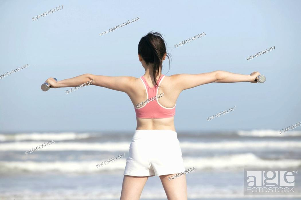 Stock Photo: Rear view of a woman stretching her arms at the seashore with dumbbells in her hands.
