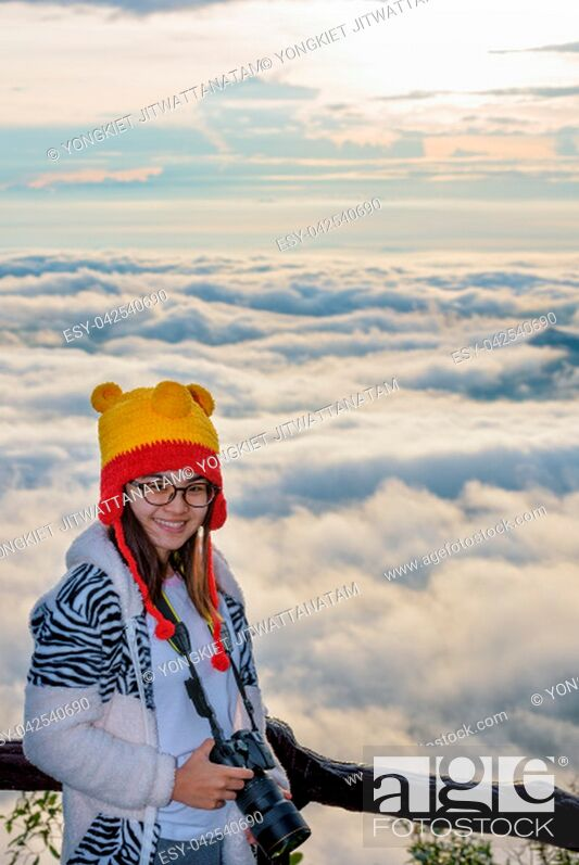 Imagen: Woman tourist holding a DSLR camera on beautiful nature landscape of fog is like the sea in the winter during sunrise background at high viewpoint Phu Ruea.