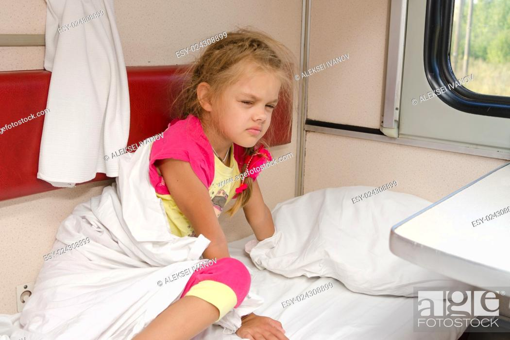 Stock Photo: The girl on the train sleepily gets out of bed on the lower place in the second-class compartment wagon.