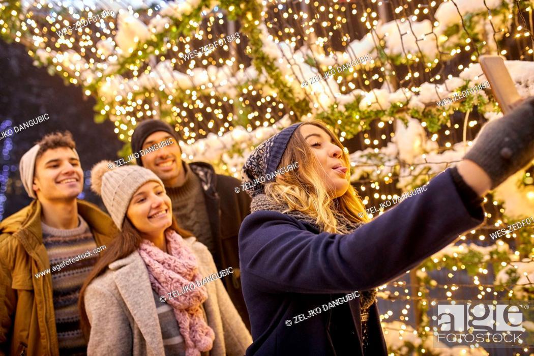 Stock Photo: Happy friends in winter decoration taking a selfie.