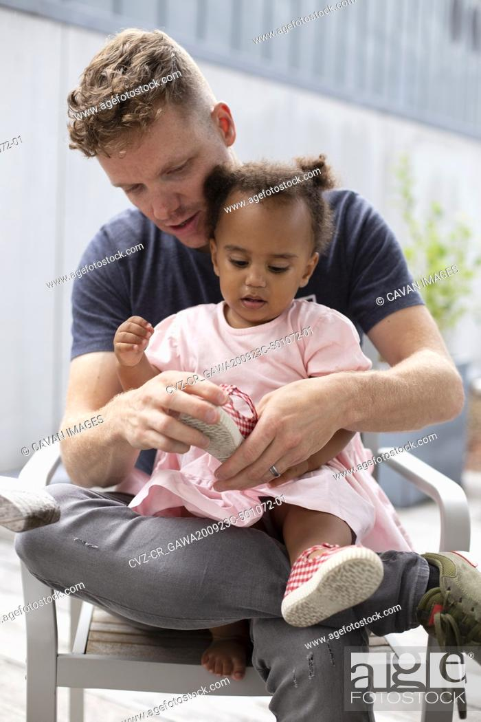 Stock Photo: A caucasian father helps his biracial daughter put her shoes on.