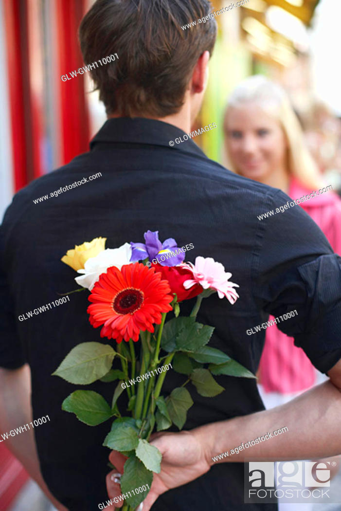 Stock Photo: Rear view of a man hiding a bunch of flowers behind his back.