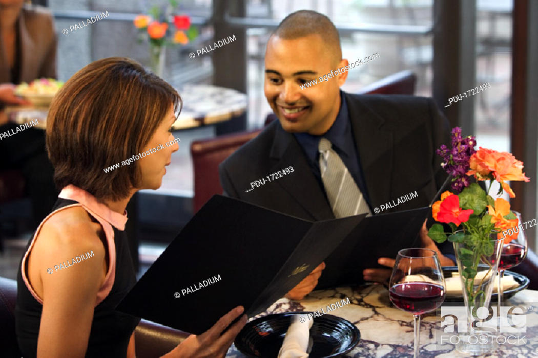 Stock Photo: A couple talks while looking at the menu at a nice restaurant.