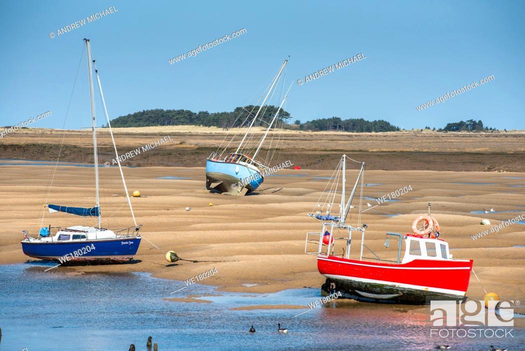 Stock Photo: Colourful boats marooned on sandbanks at low tide on East Fleet river estuary at Wells next the sea, North Norfolk coast, East Anglia, England, UK.