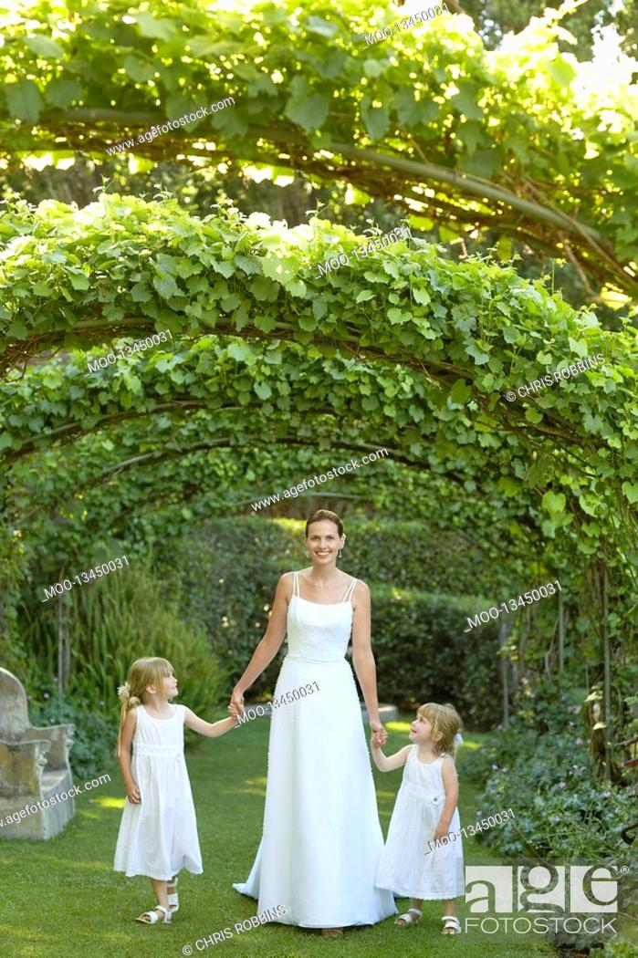 Stock Photo: Two young girls and mid adult bride under ivy arches holding hands portrait.
