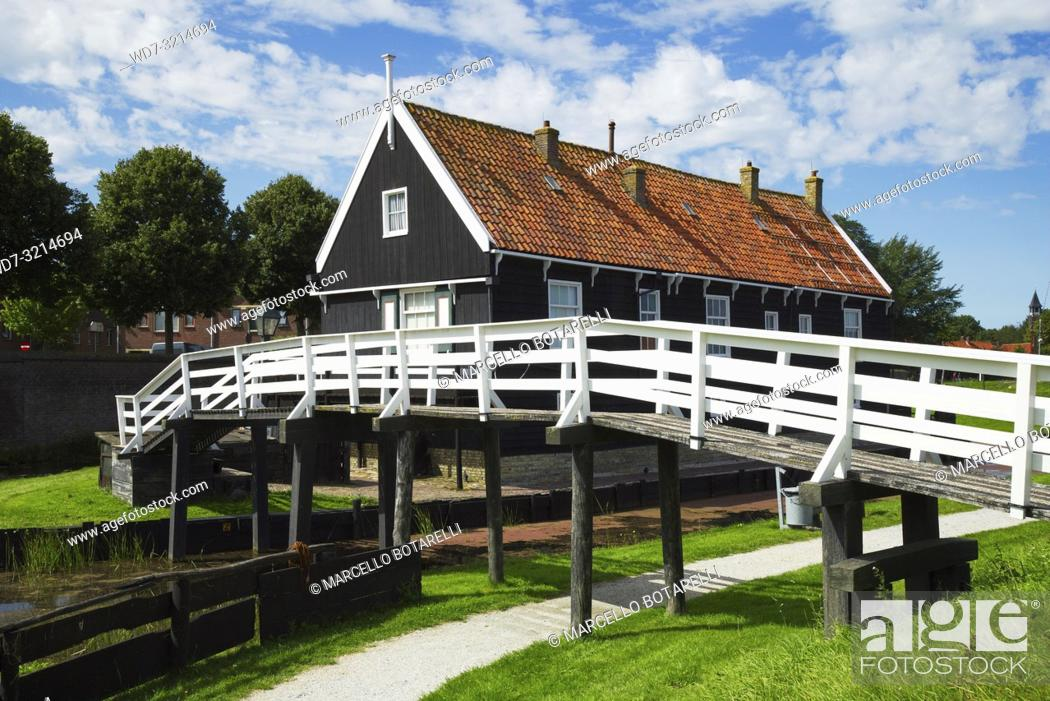 Stock Photo: Traditional fisherman's house with white wooden bridge, trees and grass, clouds and blue sky in Enkhuizen, small town in Netherlands.