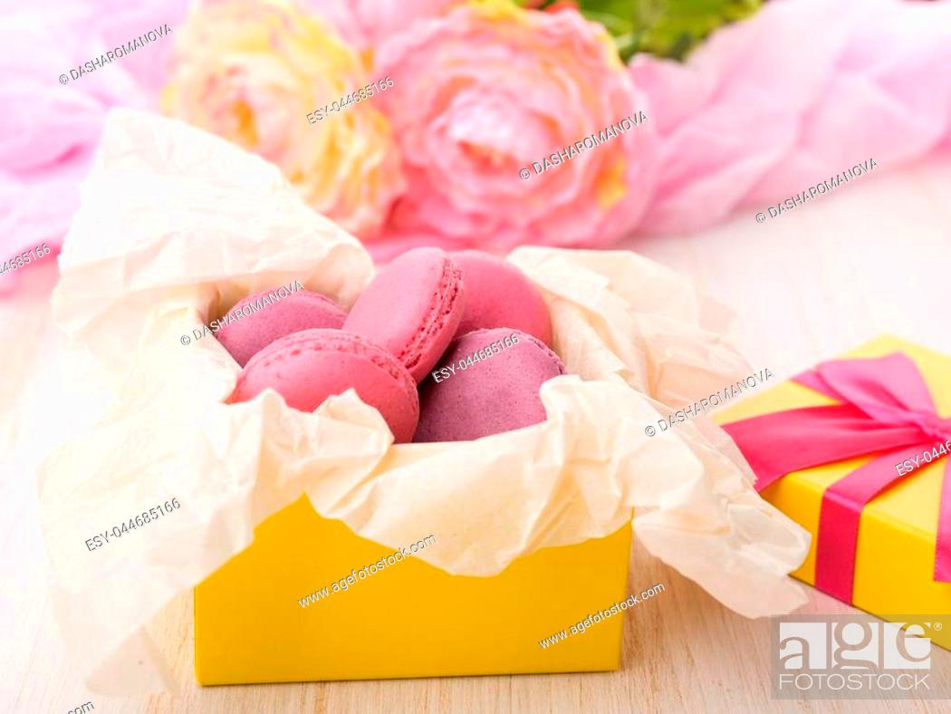 Stock Photo: Sweet cakes in a yellow box on a wooden table. Pink flowers.