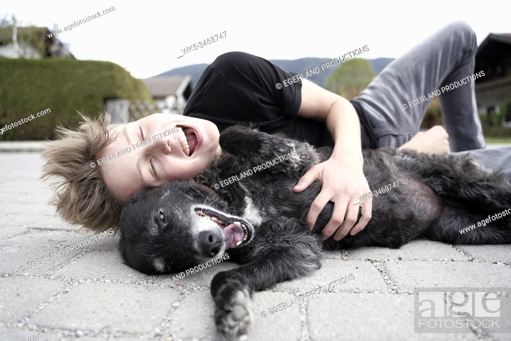 Stock Photo: Teenager playing with his dog, in Gaissach, Bavaria, Germany.