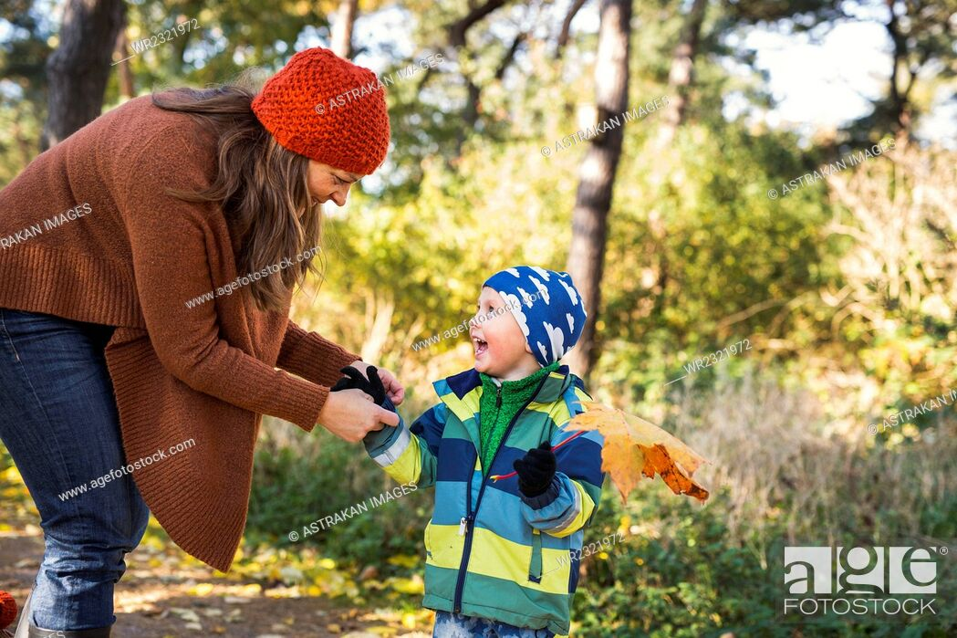 Stock Photo: Mature mother with playful boy holding leaf in forest during autumn.