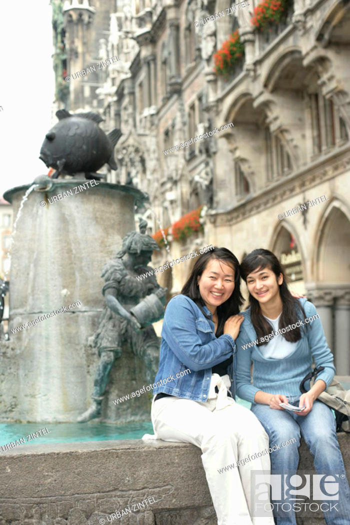 Stock Photo: Two young Asian women sitting on the brim of a fountain, focus on foreground.
