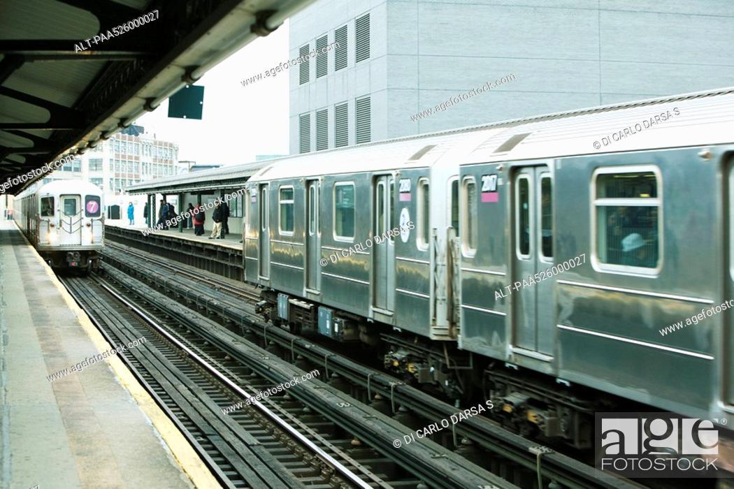 Stock Photo: Commuters waiting for subway on elevated train platform, IRT Flushing Line of New York City Subway.
