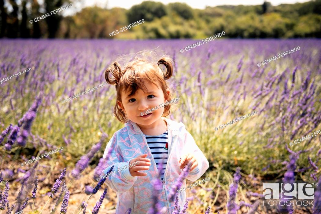 Stock Photo: France, Grignan, portrait of smiling baby girl standing on lavender field.
