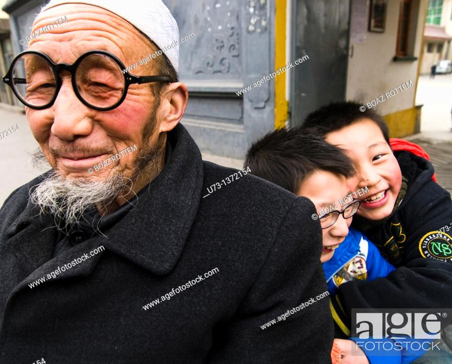 Stock Photo: A Hui Muslim man with his two grandchildren.