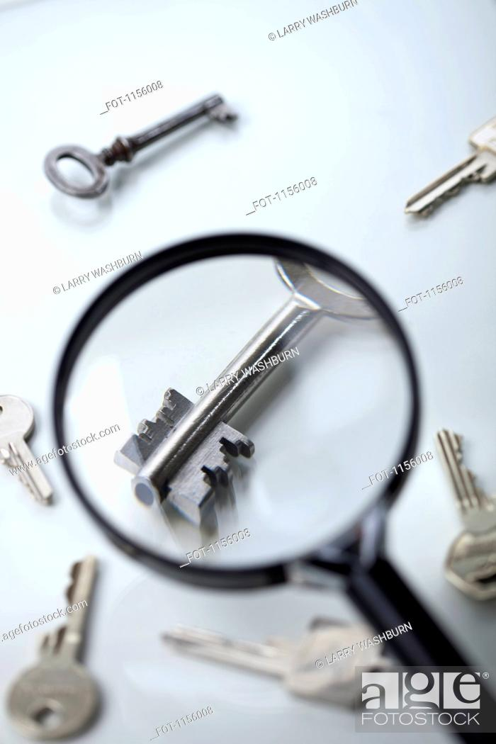 Stock Photo: A key lying amongst many being magnified by a magnifying glass.