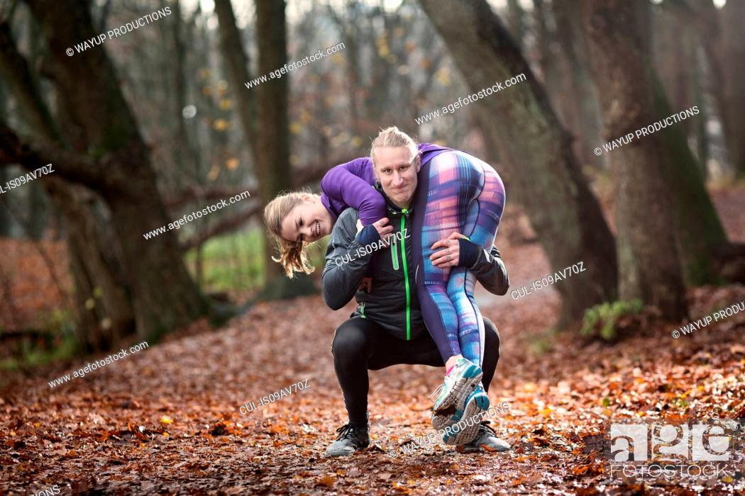 Stock Photo: Mid adult man crouching in forest carrying young woman on shoulders looking at camera smiling.