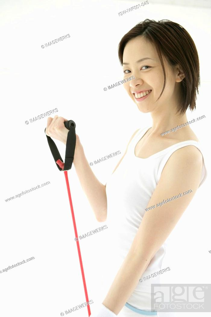 Stock Photo: A young woman smiles as she uses the stretching rope for an exercise.