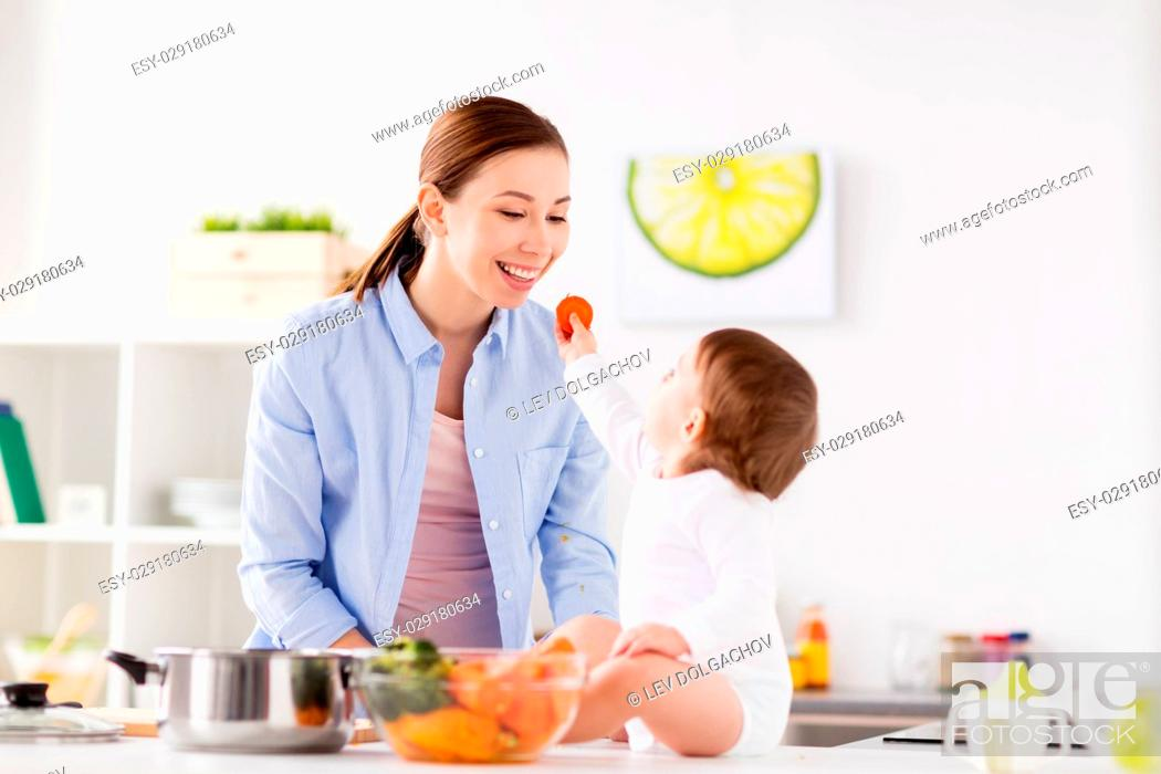 Stock Photo: family, food, healthy eating, cooking and people concept - little baby feeding his mother with carrot at home kitchen.
