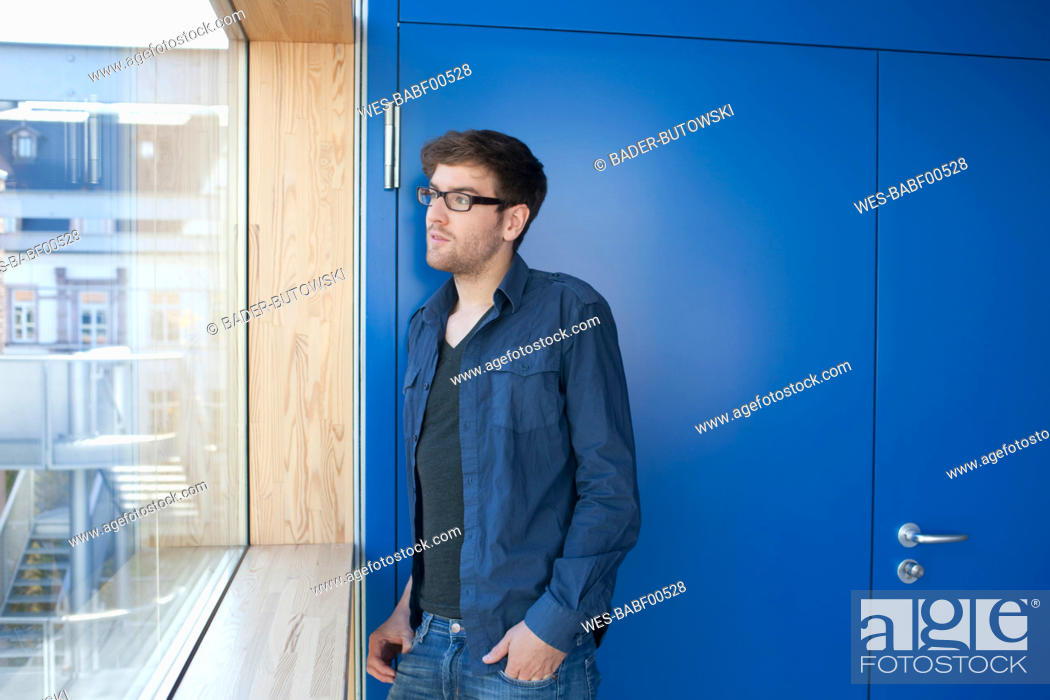 Stock Photo: Germany, Leipzig, Young man looking through window.