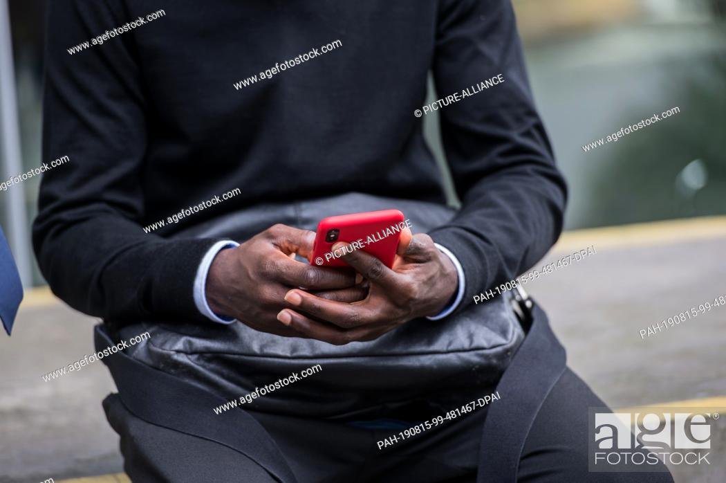 Stock Photo: 15 August 2019, Hessen, Frankfurt/Main: Bakery Jatta (HSV) sits on a wall on the DFB premises and operates his smartphone.