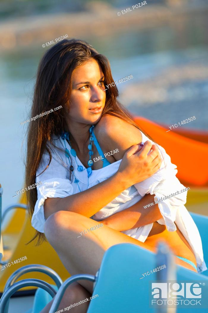 Stock Photo: Attractive young woman on the beach is enjoying a warm sunset light.