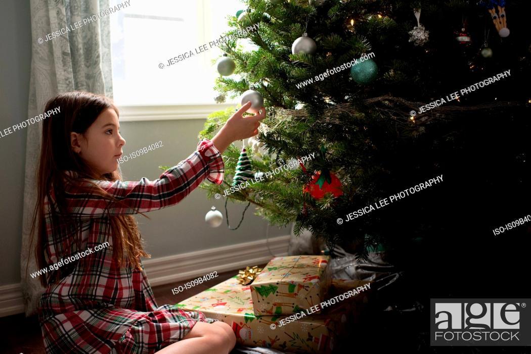 Stock Photo: Girl decorating christmas tree with christmas decorations.