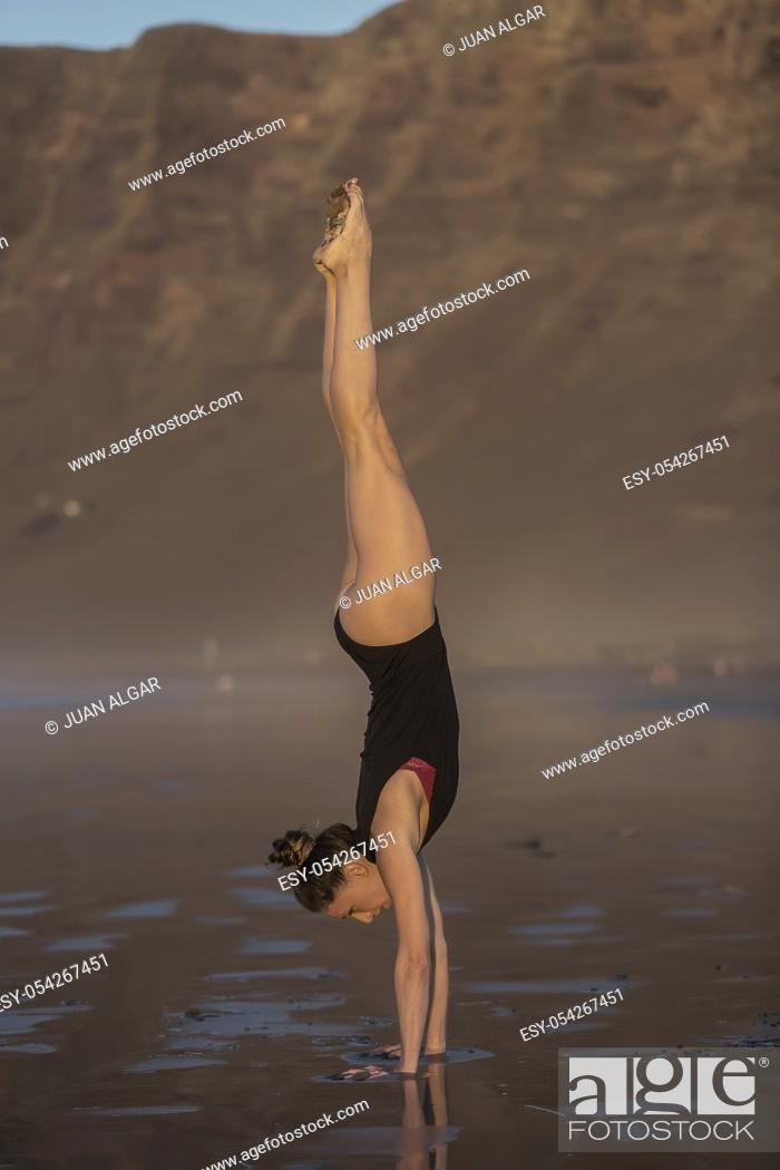 Stock Photo: Side view of slim woman balancing in handstand on wet sand of beach.