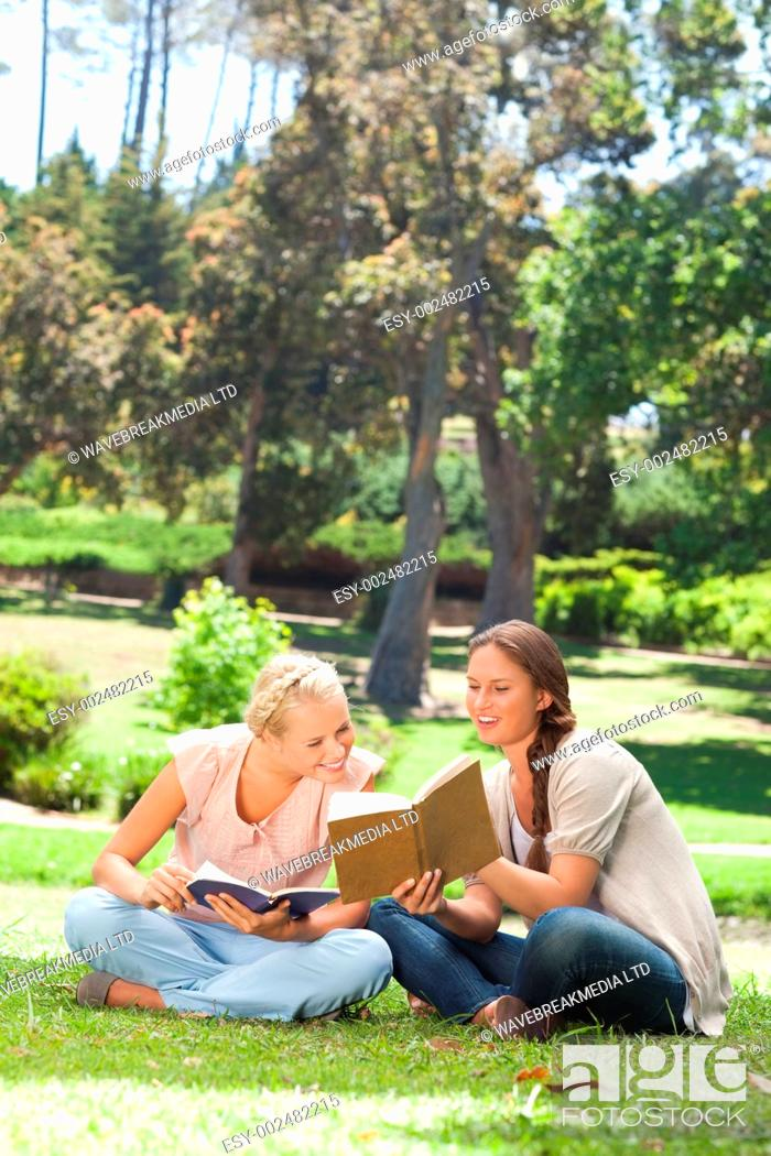 Stock Photo: Young woman showing her friend something in her book.