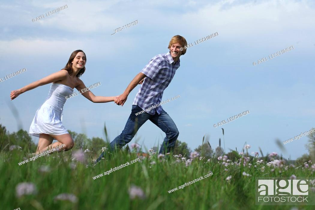 Stock Photo: couple, couples, man, woman,boy, girl, young, twosome, nature, grassland ,meadow,summer, sun,sunny,sunshine,flowers,embracing, love,loving,arms,arm,holding.