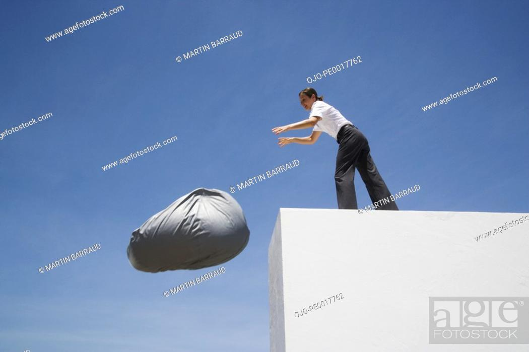Stock Photo: Businesswoman tossing beanbag chair off wall outdoors.