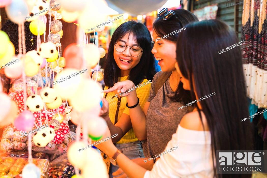 Stock Photo: Tourists admiring decorative lights in bazaar, Bangkok, Thailand.