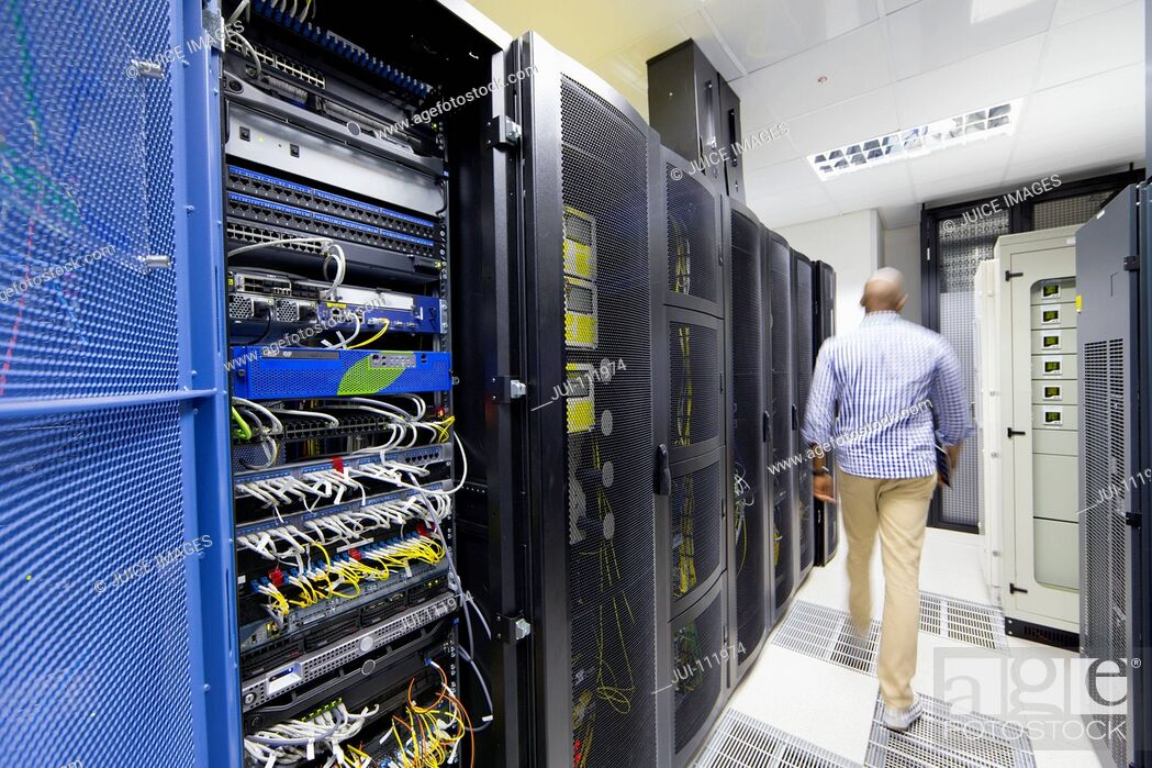 Stock Photo: Technician with digital tablet walking away from camera in server data centre.