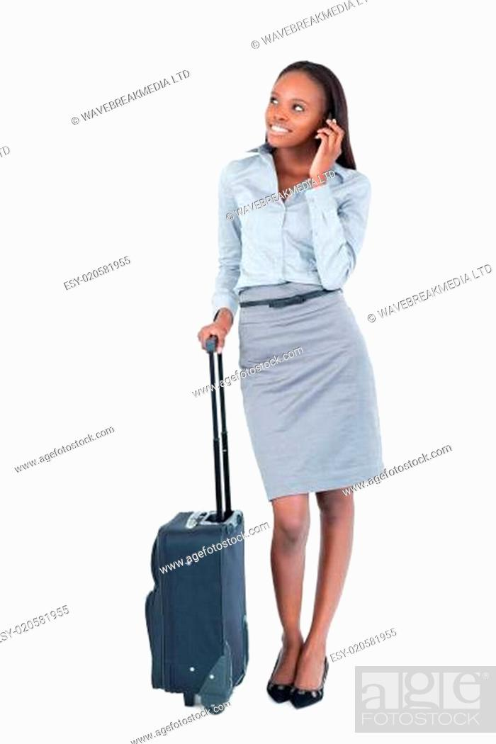 Stock Photo: Portrait of a cute businesswoman with a suitcase making a phone call.