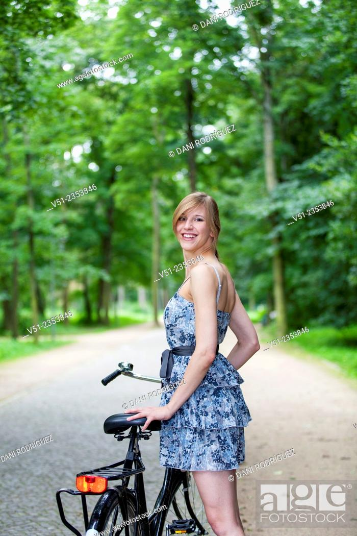 Stock Photo: Happy blonde woman with bicycle in park smiling at camera.