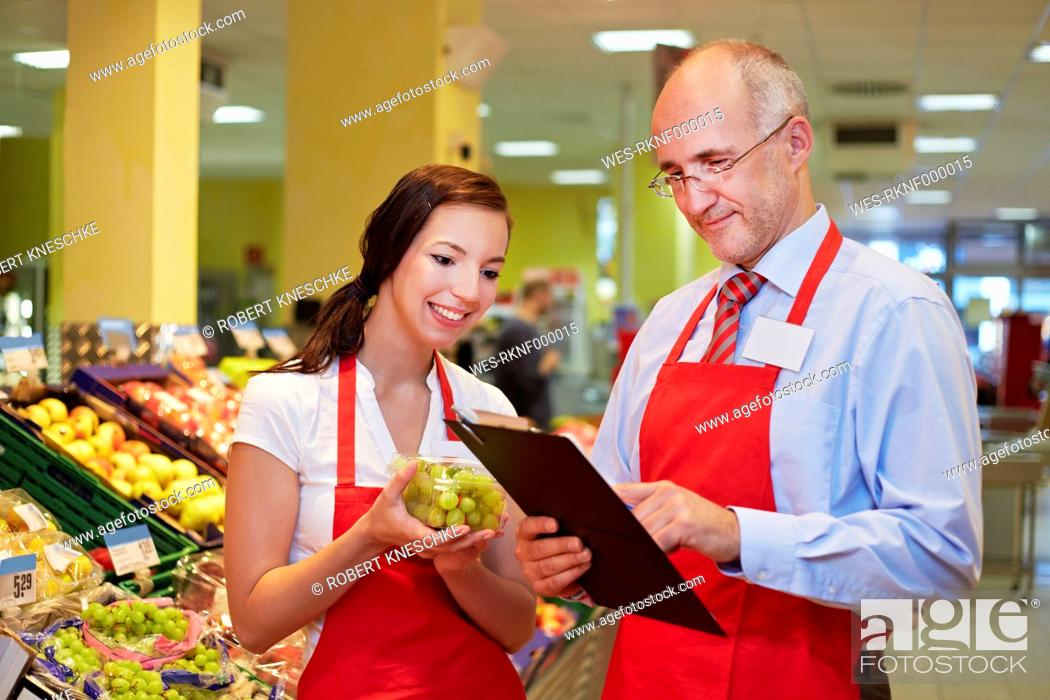 Stock Photo: Germany, Cologne, Man and woman with grapes in supermarket.