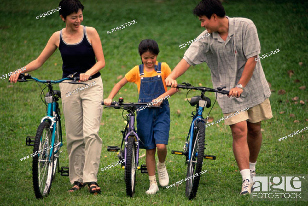 Stock Photo: Parents with their daughter walking with bicycles in a park.