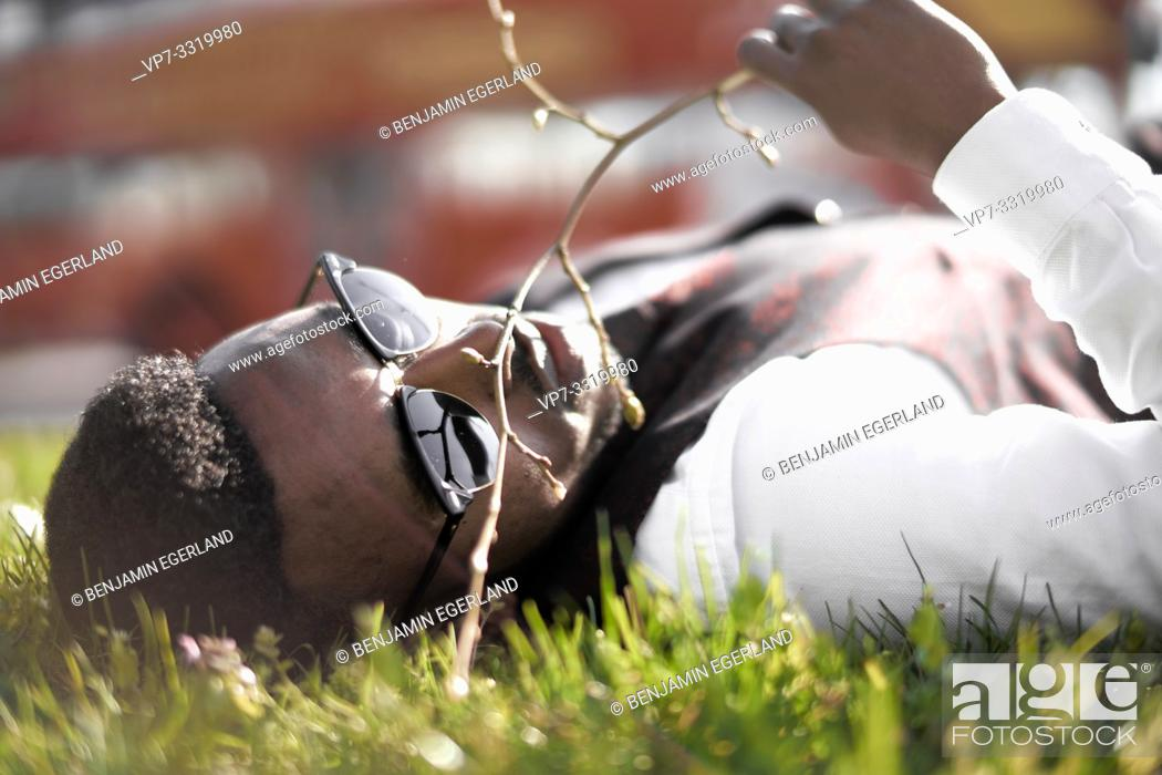 Stock Photo: well-dressed African man laying in nature grass in city, in Munich, Germany.