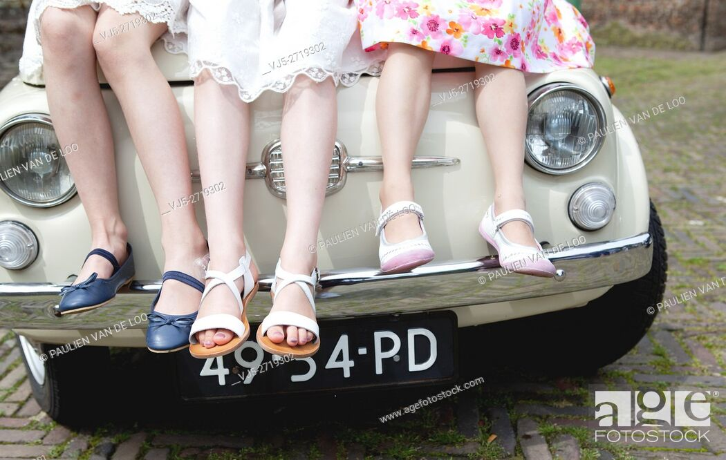 Stock Photo: Helmond, Netherlands, 3 little girls with flowers all dressed up sitting on a vintage car.