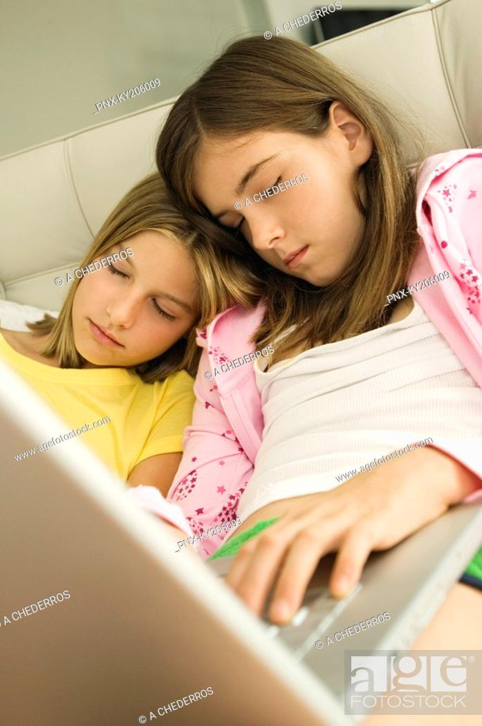 Stock Photo: Two girls sleeping with a laptop on their laps.