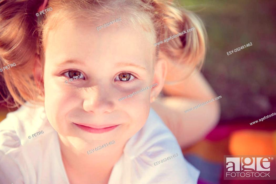 Stock Photo: Excited face of pretty small girl in summer park.