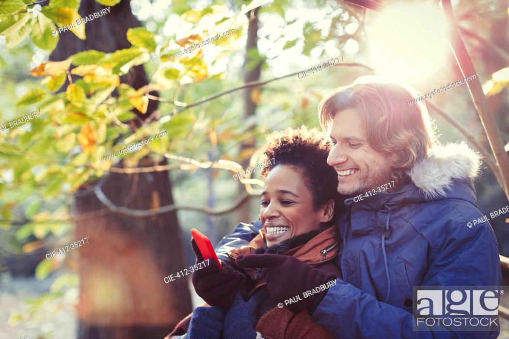 Photo de stock: Smiling couple using cell phone in sunny autumn park.